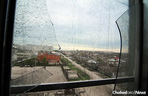 """A 2015 file photo of a smashed window in a Mariupol Jewish community member's apartment. The official death count was around 30, but Jewish community member Natasha Ralko—whose windows were blown out while she was in her living room with her daughter and 8-month-old infant, and whose kitchen was heavily damaged—was convinced that the number is higher. """"There were at least 30 bodies just down there around the parking lot,"""" she said at the time. (Photo: Jonathan Alpeyrie for Chabad.org)"""