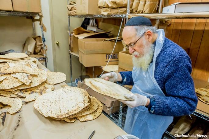 Packing traditional round shmurah matzah. (Photo: Eliyahu Parypa/Chabad.org)