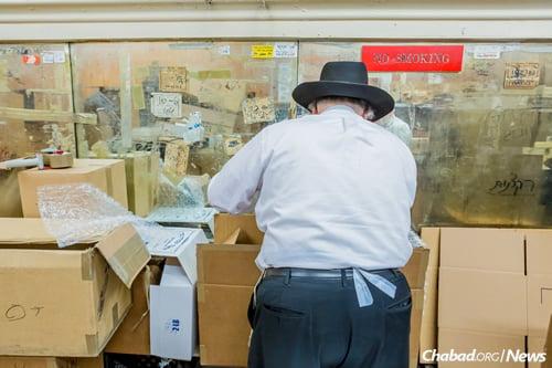 Packing up boxes of handmade shmurah matzo. (Photo: Eliyahu Parypa/Chabad.org)