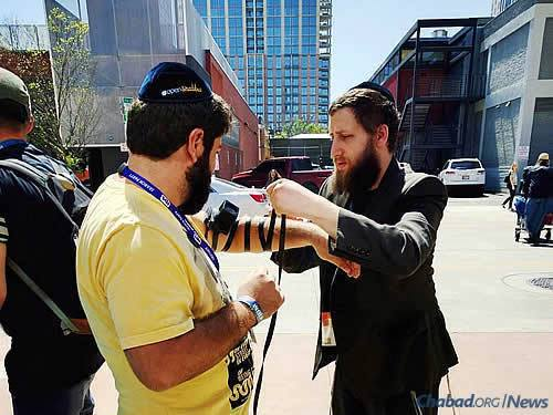 Lightstone wraps tefillin last year at SXSW in Austin. He, his wife and the Levertovs have been hosting electronics-free Shabbat dinners at the festival since 2010, and this year, a Purim party is also on tap.