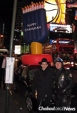 The 8-foot, car-top Chanukah menorah that caught the interest of crowds in Times Square, including this police officer. Kule covered the costs to purchase them.