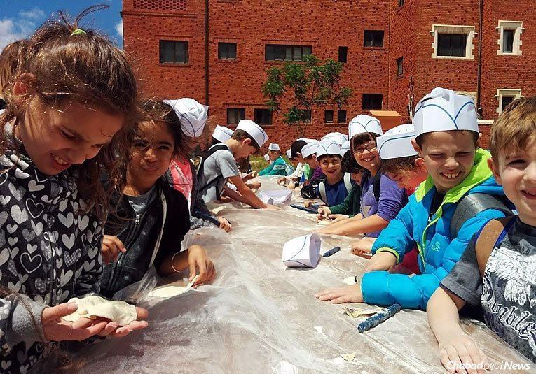 Israeli students dig into the activity at hand: making matzah at the historic matzah bakery in Kfar Chabad, founded in 1950. Thousands of people of all ages from throughout the country visit in the weeks before Passover, which this year begins on the night of Monday, April 10. (Photo courtesy of the Kfar Chabad bakery)