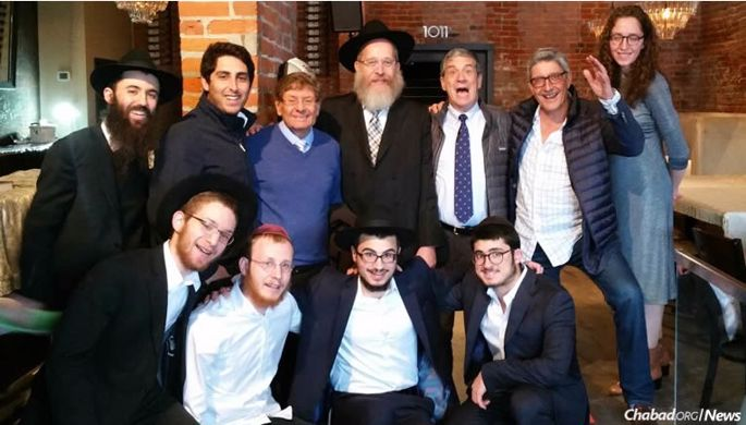 A group gathers before last year's Berkshire Hathaway annual shareholders meeting in the space that serves as a pop-up Chabad center. Top, from left: Avraham Kenner, Andrew Greenwall-Cohen, Arnold Basserabie, Rabbi Mendel Katzman, Gary Yarus, David Cicurel and Rochi Katzman. Bottom, from left: Zelig Katzman, Yossi Katzman, Yisroel Benshimon and Zalmy Cohen