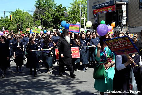 Rabbi Yosef Minkowitz, center, today head of school at Beth Rivkah Academy in Montreal, leads a group of students in the annual Lag BaOmer parade in Montreal.