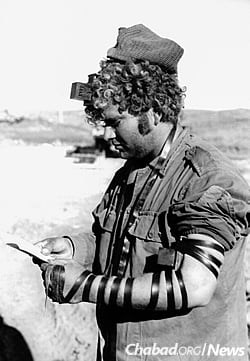 A soldier recites Shema Yisrael after having put on tefillin with a Chabad Chassid. (Photo: JEM/The Living Archive)