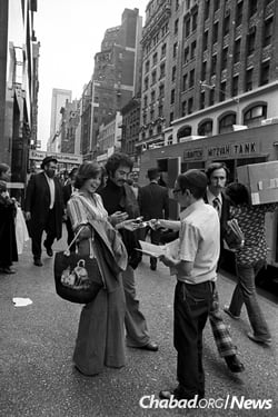 A yeshivah student offers Shabbat candles to a Jewish woman in New York City after the Rebbe launched his Shabbat candle campaign in August of 1975. (Photo: JEM/The Living Archive)