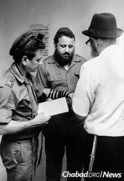 Rabbi Berke Wolff, center, was the energetic young Chabad activist who got the tape of the Rebbe's talk from the airport and spread it throughout the country. Here, he is seen putting tefillin on with military personnel in the late 1960s/early 1970s. (Photo: JEM/The Living Archive)