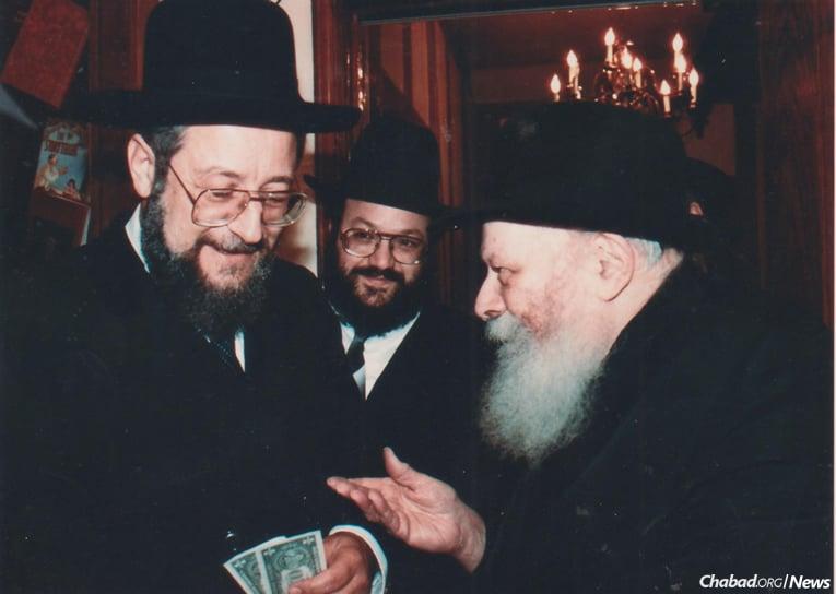 Rabbi Yisrael Meir Lau, left, receives dollars and blessings from the Rebbe, as Rabbi Yosef Gerlitsky looks on.