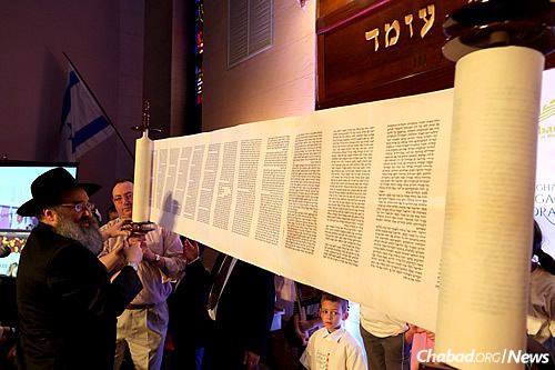 Holding the scroll up for all to see. According to tradition, the moments after a Torah is completed is considered an auspicious time to pray to G-d for blessings. (Photo: Chabad of Binghamton/Bentzi Sasson)