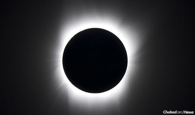 Streamers of light are often visible around the silhouette of the moon during a solar eclipse, which will take place next on Monday, Aug. 21.