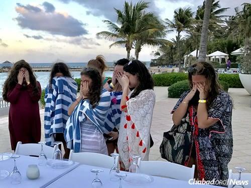 Des femmes disent la bénédiction des bougies avant la célébration du Chabbat sur la plage. (Photo: Chabad of Jamaica)