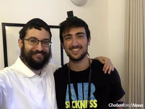 Rabbi Levi Laine, left, co-director of Chabad of Hanoi, wraps tefillin with a visitor.