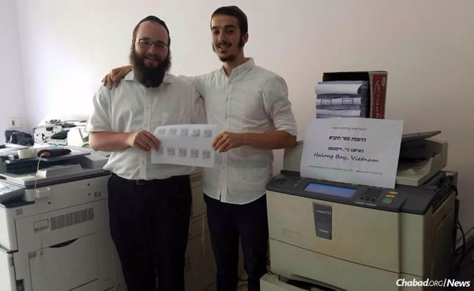 """""""Roving Rabbis"""" Shmuel Butler, left, and Ari Herson print copies of the Tanya, the foundational work of Chabad teaching, as part of their efforts this summer serving Jewish tourists and expats in Vietnam."""