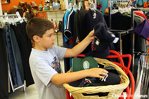 A young customer checks out baseball caps. (Photo: Len Weinstein)