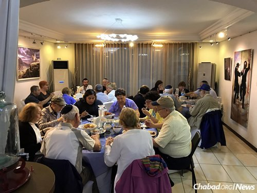 A group of summer travelers enjoys dinner at the Chabad House in Seoul.