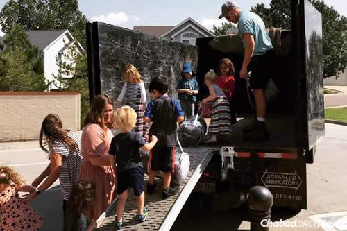 Children at the Chabad Garden Preschool help load The Junk Trunk truck owned by Nathan Schweid, who donated its use to transport 2,000 pounds of supplies valued at more than $20,000. Student Ben Davis, pictured with the kids, drove the truck to Houston.