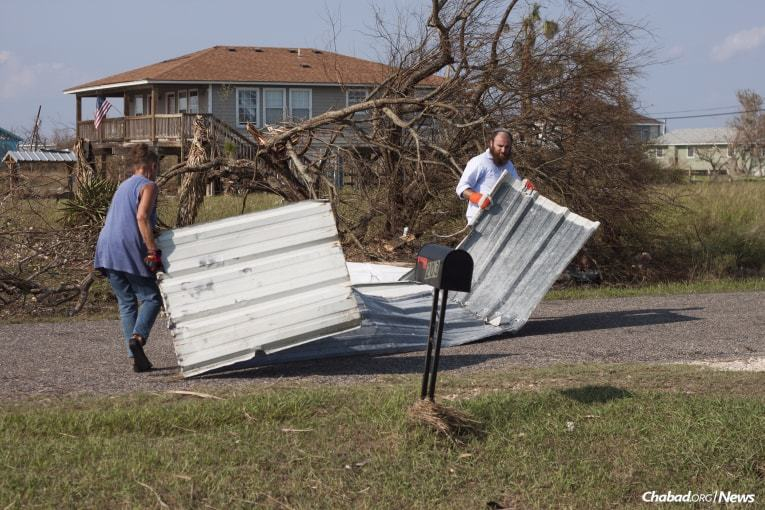 The rabbi helps remove debris with an individual affected by Hurricane Harvey in Rockport. (Photo: Verónica G. Cárdenas/Chabad.org)