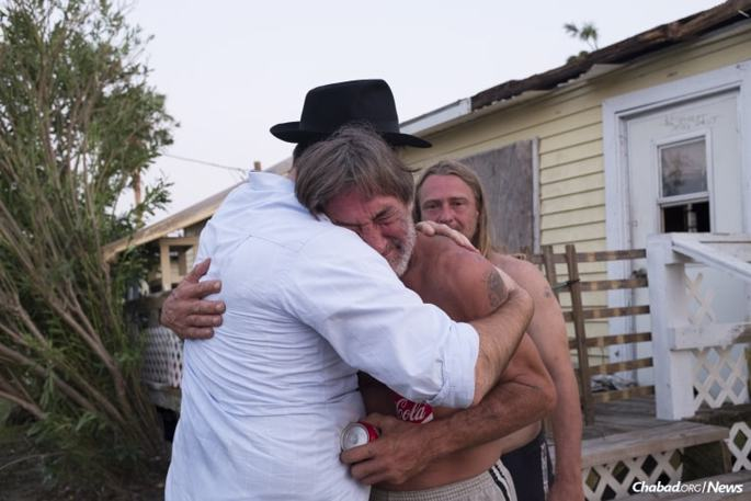 Chabad-Lubavitch Rabbi Naftoli Schmukler, left, of Corpus Christi, Texas, embraces and comforts Ed Flower, a local homeowner, who together with his brother, barely survived the hurricane in Port Aransas, Texas, on Thursday, Aug. 31, 2017. (Photo: Verónica G. Cárdenas/Chabad.org)