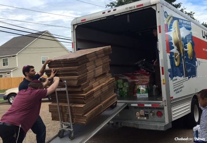 Cardboard boxes, in which clothes can be stored while people are in the process of cleaning up their homes, are loaded into a truck also filled with food staples and cleaning supplies for storm victims