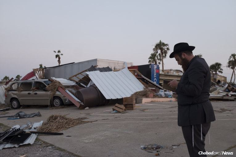The rabbi prays in front of a destroyed business in the city of Port Aransas, Texas. (Photo: Verónica G. Cárdenas/Chabad.org)