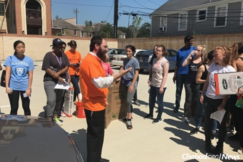 Rabbi Shmuel Slonim briefs student volunteers from Rice on work that needs to be done.