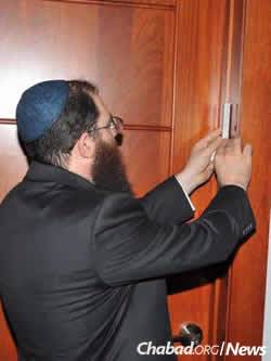 Affixing a mezuzah on the new building, which soon would be assaulted by a Category 5 hurricane.
