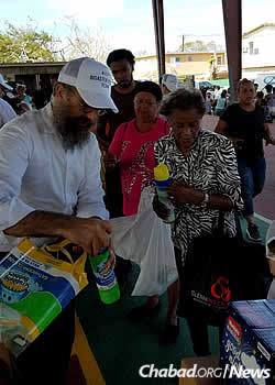 The rabbi hands out cleaning supplies to a line of waiting people.