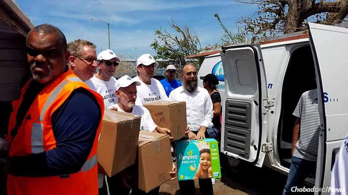 Rabbi Mendel Zarchi, right, co-director of Chabad Lubavitch of Puerto Rico, and assistants on the ground have been working nonstop on recovery efforts after Hurricane Maria plowed over the island on Sept. 20. A 30-hour Jewish fundraising campaign was also launched on Oct. 16 to assist residents, many of whom remain without power and potable water.