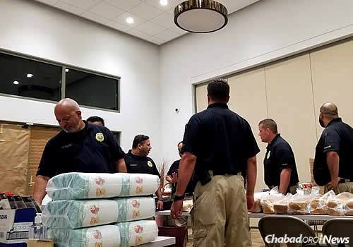 Officers organize donated goods for distribution gathered at the Chabad center.