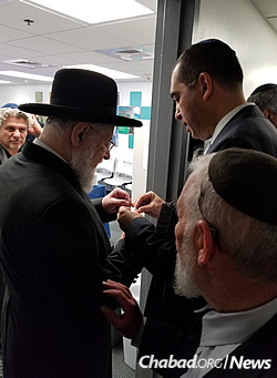 Rabbi Lau hangs a mezuzah on the doorpost of the El Al offices at Miami International Airport on Nov. 1, the day direct flights to Israel began.