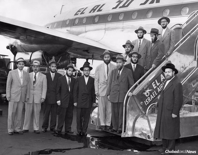 The Rebbe's shluchim stand by the El Al airplane on the tarmac in New York before heading off to Europe. Starting from second from left: Nisson Mindel, Yehuda Krinsky, Shlomo Kirsh, Sholom Ber Shemtov, Dovid Schochet, Rabbi Chaim Mordechai Aizik Hodakov, Sholom Ber Butman, Yosef Rosenfeld, Faivel Rimler, Avraham Korf and Shmuel Fogelman. (Photo courtesy of Kehot Publication Society)