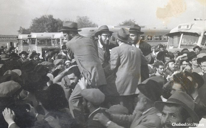 Thousands of Chassidim greeted the group upon their arrival in Israel, where in the midst of the dancing, they were lifted onto the shoulders of citizens. Buses that brought the greeters to the airport can be seen in the background. (Photo courtesy of Yimei Temimim Archive)