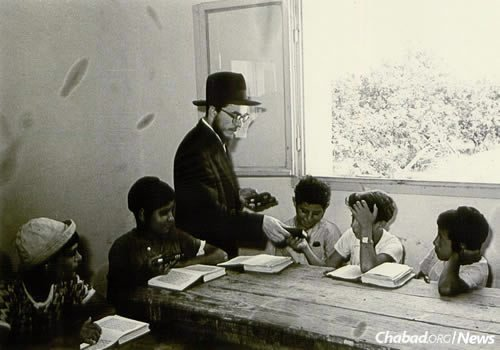 Rabbi Sholom Ber Shemtov distributes a special Tanya to Jewish children at a Chabad school. (Photo courtesy of Yimei Temimim Archive)