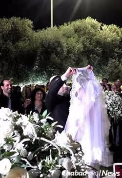 The groom lifts the bride's veil.