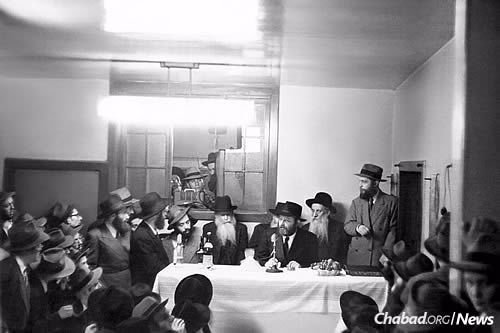 Making a siyum at farbrengen in 1952 led by the Lubavitcher Rebbe, seated at the table. Rabbi Meir Ashkenazi is seated behind him, to the right. (Photo: JEM/The Living Archive)