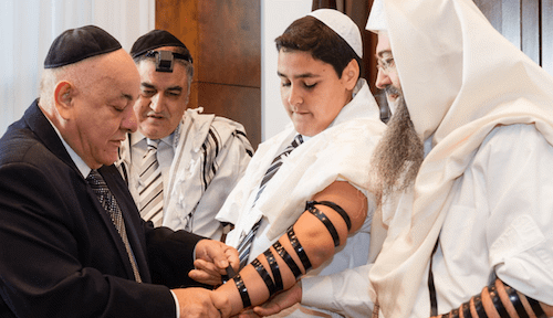 Tradition passed down to another generation: A grandfather helps his grandson don his tefillin (Credit: Serraf Studio)