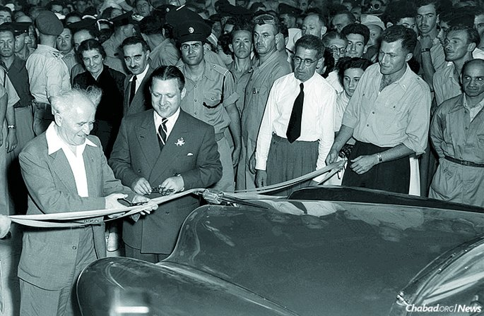 """Israeli Prime Minister David Ben-Gurion, left, cuts the ribbon at the opening of the Kaiser-Illin auto plant in Israel as its owner, Efraim Illin, a titan of Israeli industry, looks on. An interview with Illin is one of 41 accounts showcased in """"My Story,"""" a collection of first-person narratives of encounters with the Rebbe—Rabbi Menachem M. Schneerson, of righteous memory—presented with photographs and related images. (Photo: Fritz Cohen/GPO)"""