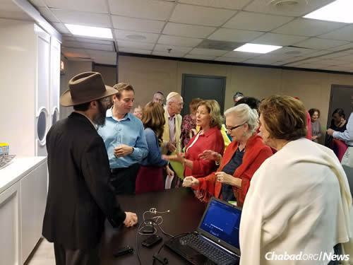 A crowd fills the room for a visual presentation about the history of Jerusalem by visiting Rabbi Avraham Stolik, co-director of Chabad of Downtown Coral Gables, Fla. To his immediate right is Marc Goldfarb, a Chabad regular.