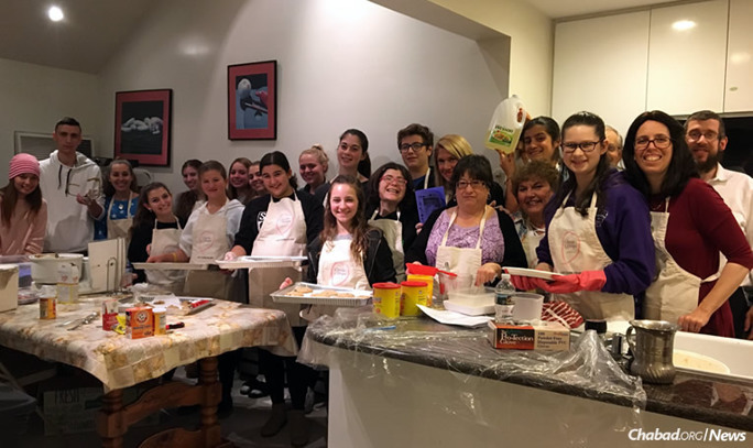 """Rabbi Shimon and Chanie Kramer, far right, who run the Chabad Center for Jewish Life in Merrick, N.Y., with teens involved in the """"Cooking for Hope"""" program. For his work, the rabbi got tapped as """"Person of the Year"""" by the Herald newspaper chain on Long Island, N.Y."""