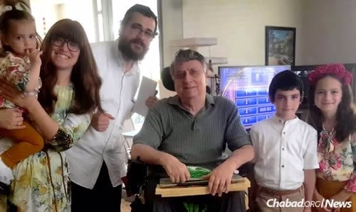 David Cohen, center, who donated funds for the media room and passed away a few weeks before its opening in September, is shown here during a visit with Rabbi Nachman Zeev and Leah Schtroks, co-directors of Chabad of Royal Palm Beach, and their children.