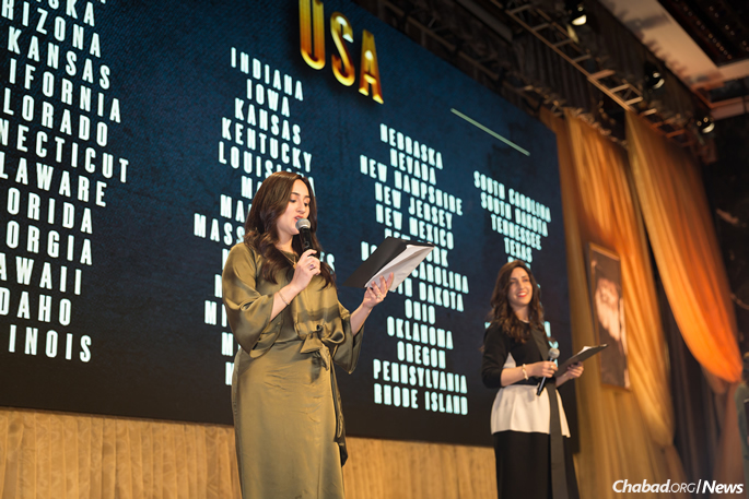 The annual roll call was read by four young new emissaries, including Mushky Feldman, left, co-director of Chabad of Iceland, and Chani Edelkopf, co-director of Chabad of Montenegro. (Photo: Chavi Konikov)