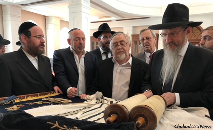 Lazar inspects a Torah scroll originally commissioned by Jewish child soldiers for their congregation and hidden away for 88 years until it, too, was regifted to the Tomsk Jewish community. Kuzhner, local donors and dignitaries look on.