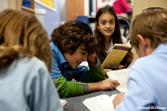 Fourth-graders discuss a novel in their literacy group.