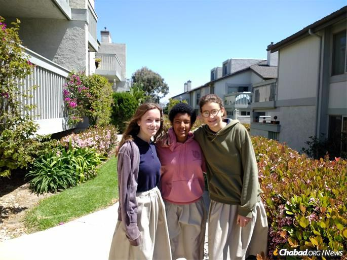 Lamplighters Jewish Academy eighth-graders Chanie Davidson, Eden Reese and Chaya Muchnik at an apartment complex in Hollywood Beach, where they distribute challah as part of a regular program.