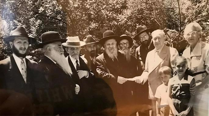 Rabbi J.J. Hecht, Rabbi Shlomo A. Kazarnovsky, Rabbi Yitzchok Perlstein, Rabbi Yosef Wineberg, the Rashag (Rabbi Shmaryahu Gurary), Rabbi Yisroel Jacobson, Rabbi Shlomo Z. Hecht, Charles Lissner, Jennie Lissner, and two grandchildren in the Lissners' Chicago backyard.