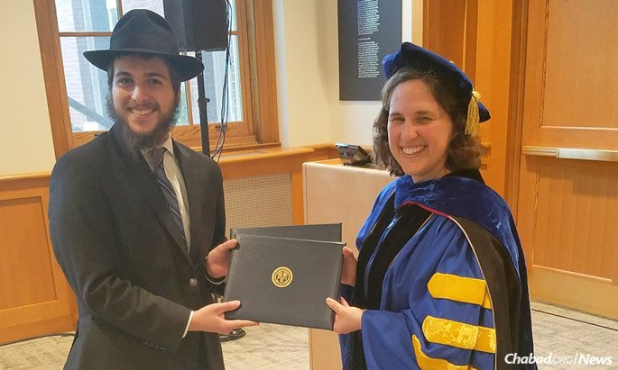 Jacob Niebloom receives his two bachelor's degrees from Dean Wendi Heinzelman, Dean of the Hajim School of Engineering and Applied Sciences at University of Rochester at an alternative graduation ceremony arranged just for him.