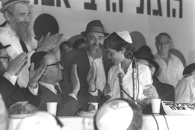The author, Avraham Godin, was arrested by Soviet occupying authorities in 1941 and released from the Gulags in 1956. He came to Israel a decade later, where he became secretary of Tzierei Agudas Chabad of Israel. Here he is pictured (center) in 1977 on the dais of the communal bar mitzvahs for IDF war orphans, watching as Prime Minister Menachem Begin applauds Shai Cohen. Photo: Moshe Milner/Israel Government Press Office.