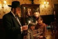 Rabbi Joshua Metzger, Shliach in Midtown Manhattan lights the Menorah with his family.