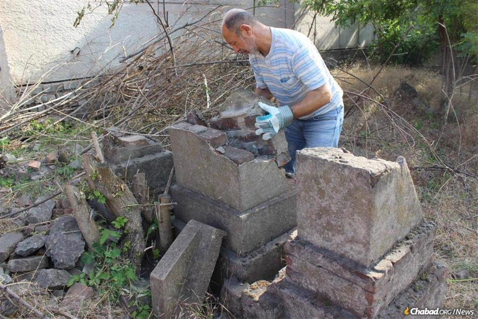 A volunteer pitches in to reset toppled headstones in the historic Jewish cemetery in Mariupol, Ukraine.