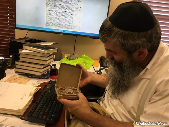 Rabbi Chaim Shaul Brook, director of Vaad Hanachos B'Lahak, shows an example of the type of tapes of the Rebbe's farbrengens that he and his team collected to help complete Toras Menachem.
